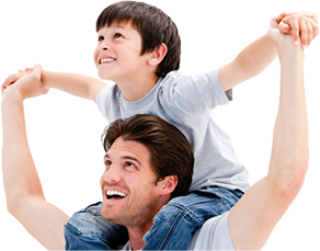 A smiling dad holds his son's arms out as the boy sits on his shoulders